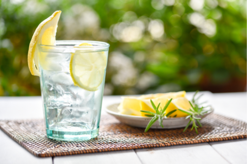 Glass of ice water with lemon and a plate of lemons on a woven placemat on a wood patio table