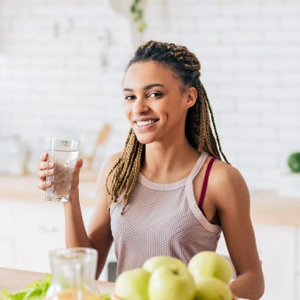 Young woman holding a glass of water in a white kitchen