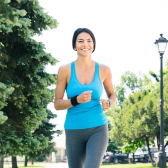 Young woman wearing a blue tank top and gray pants going for a walk in the neighborhood park