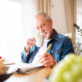 Older man wearing a jean jacket sitting at a kitchen table drinking coffee and solving a newspaper puzzle