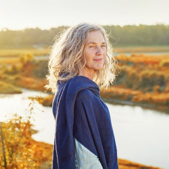 Older woman with blonde wavy hair and a purple shawl standing by a forest lake