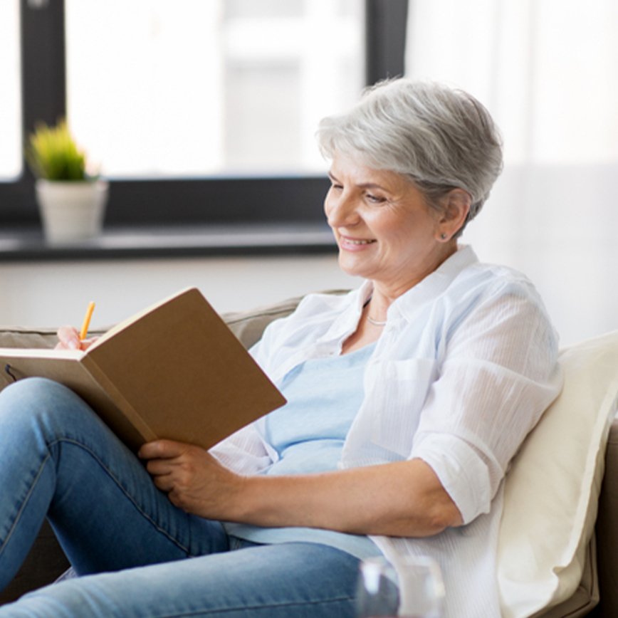 Boost Your Brain – Middle-aged woman sitting on couch and writing in a journal