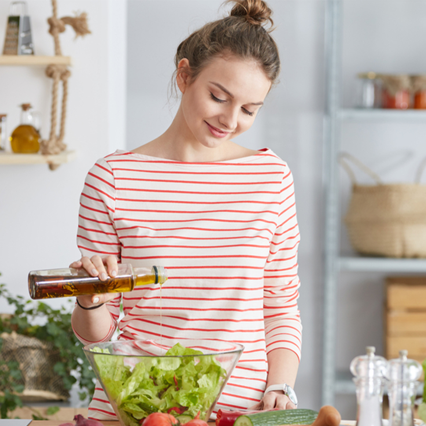 Enhances Gut Health – Young woman adding vinaigrette to a bowl of salad in the kitchen