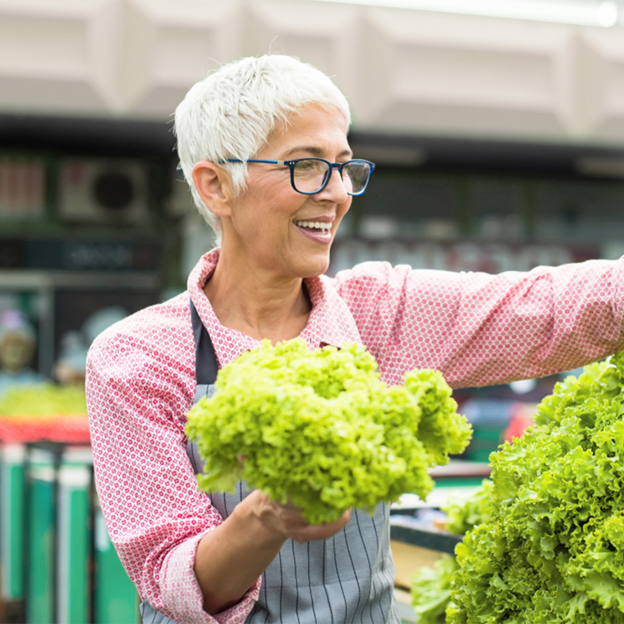 Powerful Nutritional Support — Older woman choosing romaine lettuce