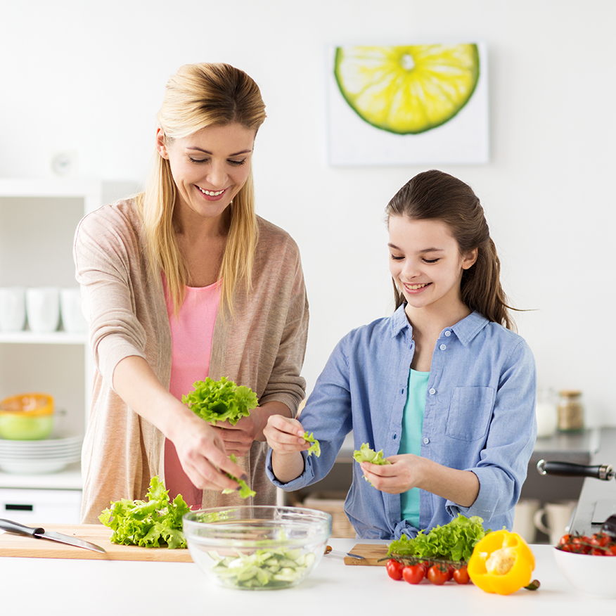 Supports the Gut – Mother and teenage daughter preparing a salad in the kitchen