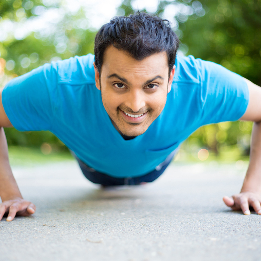 Encourages Regularity – Young man in plank position on cement