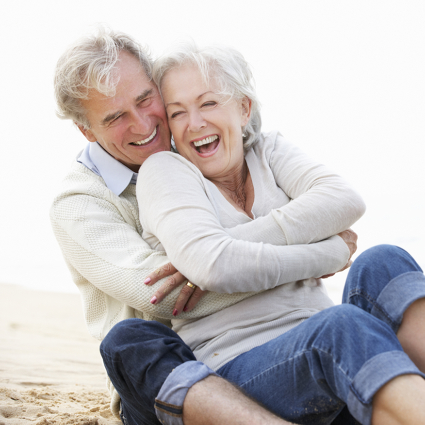 Feel Young – Elderly couple sitting in the sand on the beach happily embracing and laughing