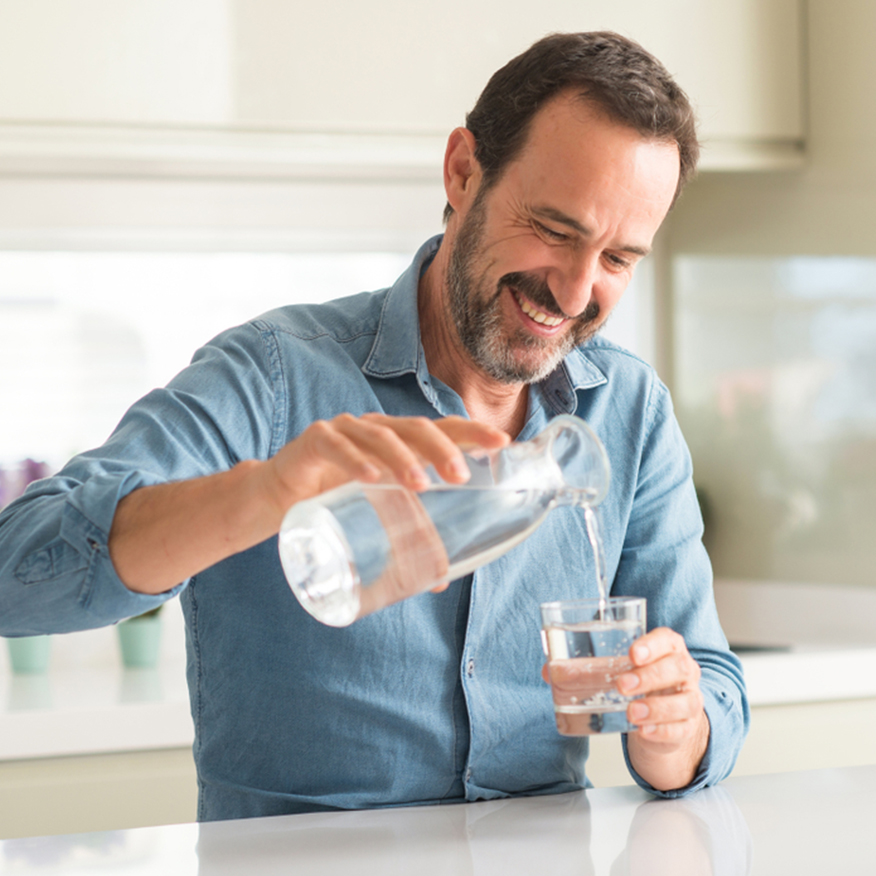 Most Effective Ingredients – Man pouring a glass of water in the kitchen
