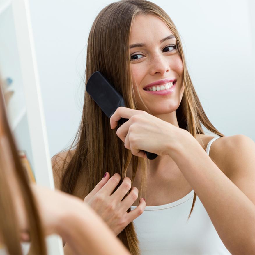 Renforce les cheveux - jeune femme se peignant les cheveux