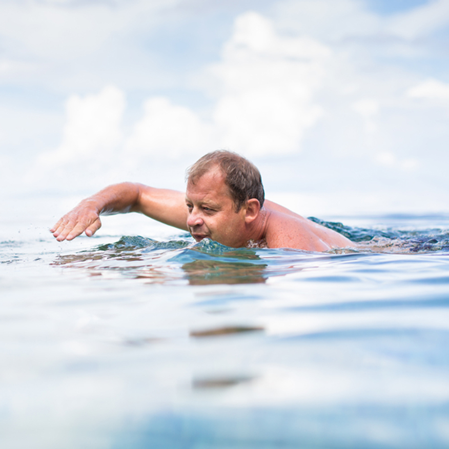 Helps Cardiovascular Health — Middle-aged man swimming at the beach