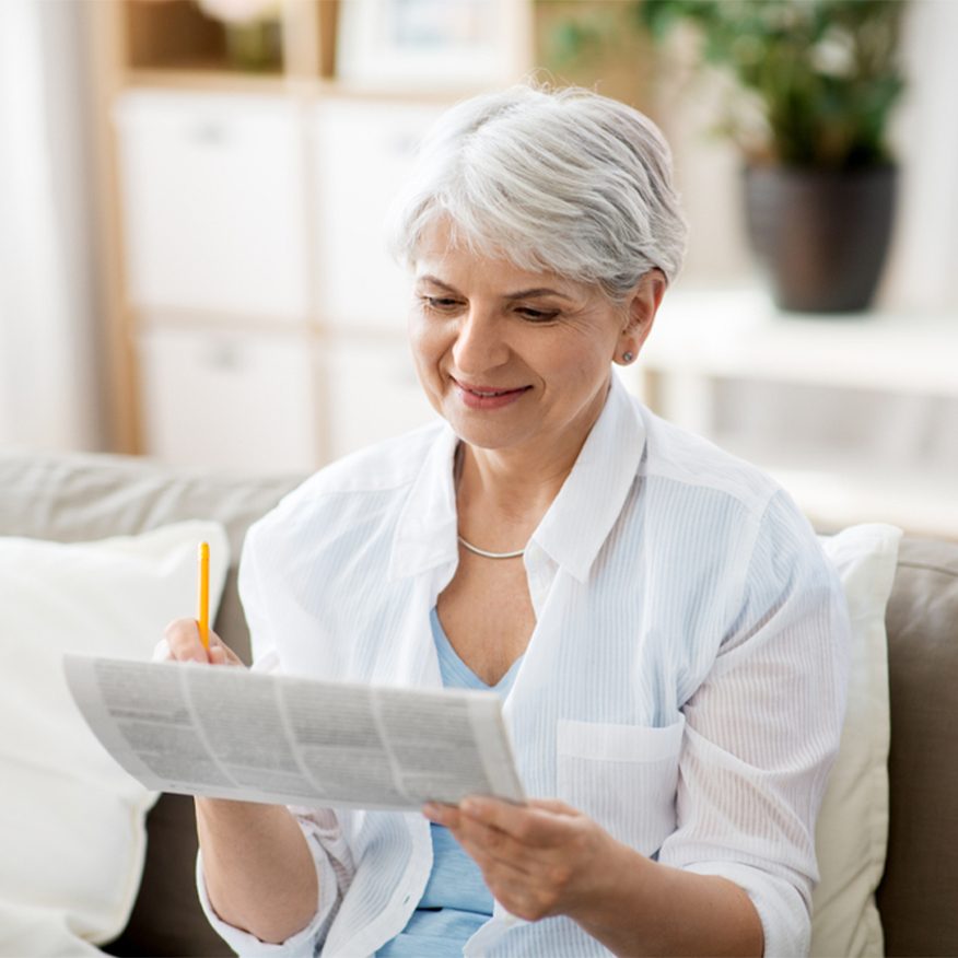 Support Your Brain – Middle-aged woman sitting on couch solving newspaper puzzles