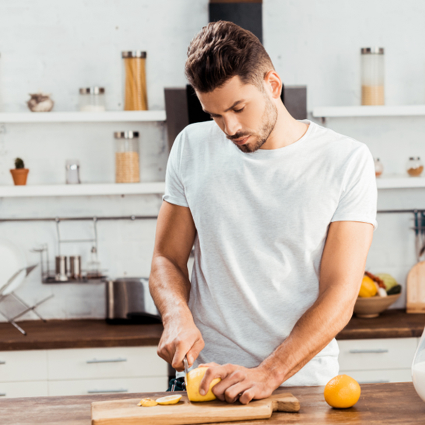 Promotes Detoxification – Man cutting up lemons on a cutting board in the kitchen
