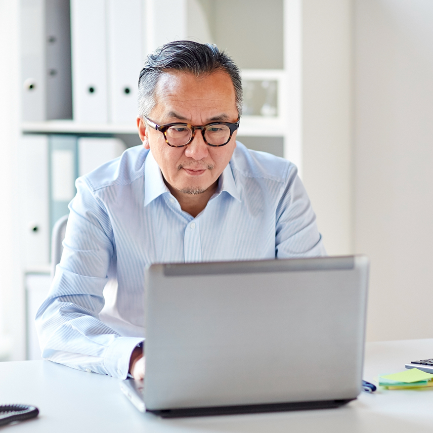 Fewer Digestive Ailments – Middle-aged man sitting at desk and working on laptop