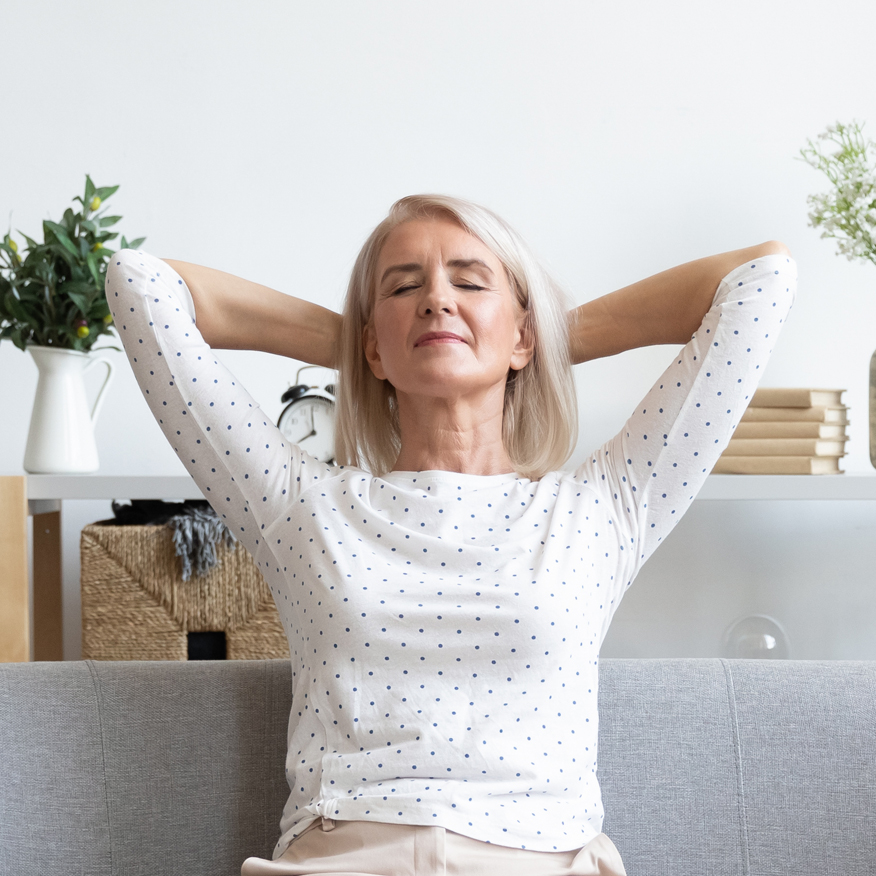 Supports Mental Well-Being – Middle-aged woman resting on couch with eyes closed and arms behind her head