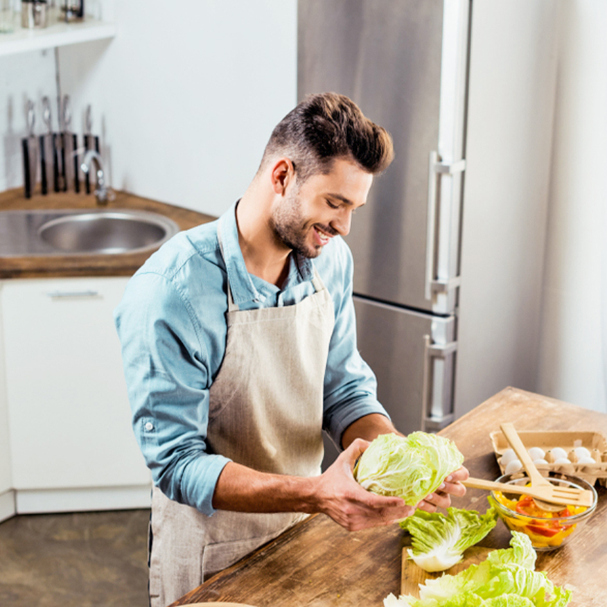 Enjoy Better Digestion – Man preparing salad in the kitchen