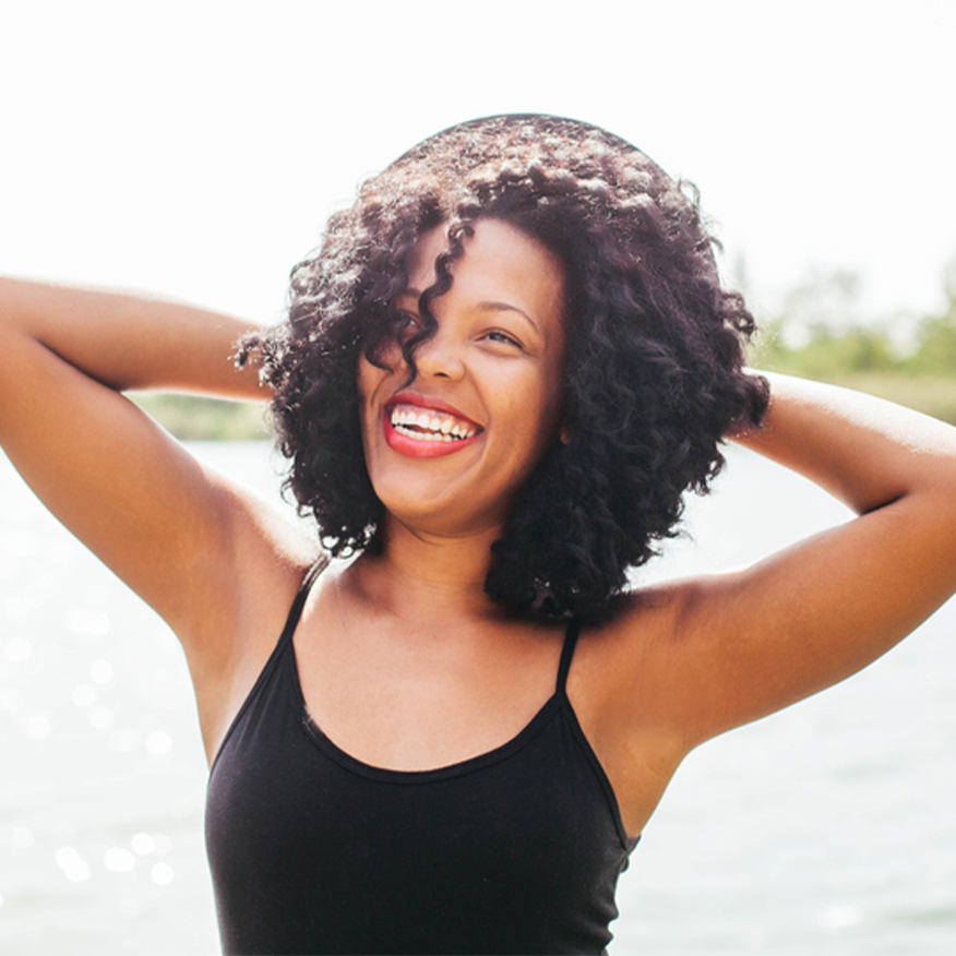 Feel Great – Woman near lake with arms stretched behind her head