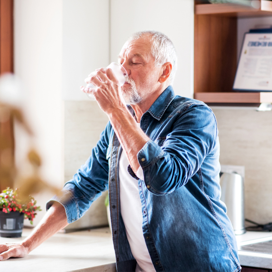 It's Easy – Older man drinking a glass of water in the kitchen