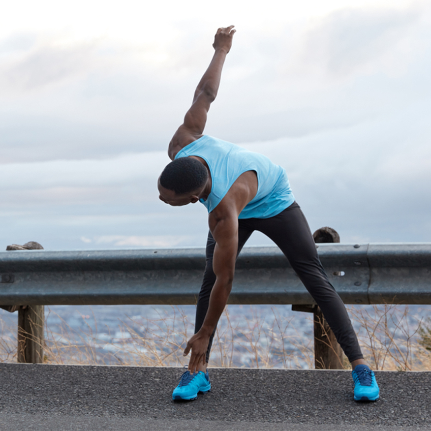 Healthy Bones and Teeth – Man stretching in front of guardrail near the water
