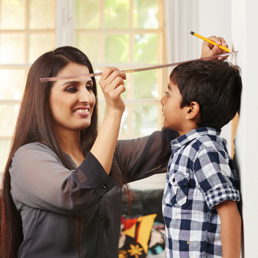 Promotes Healthy Growth – Mother measuring son's height up against a wall