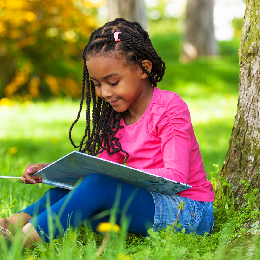 Cognitive Development – Young girl sitting in grass under tree and reading a book