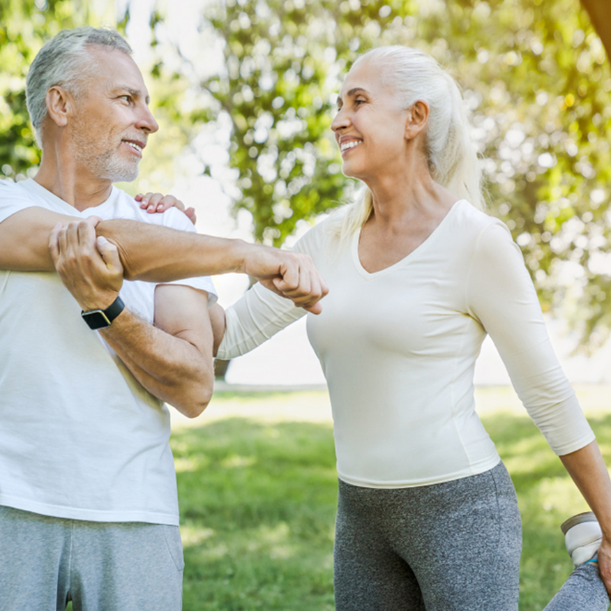 Supports Brain Health – Middle-aged couple stretching together outdoors