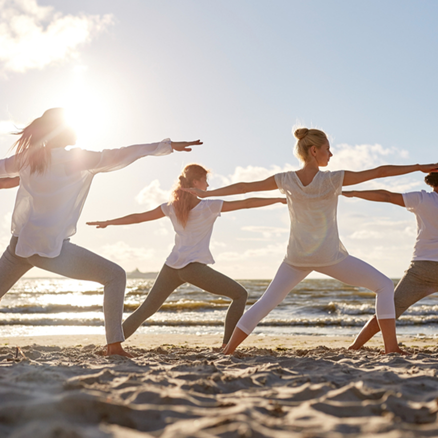 Fills the Gaps In Your Diet – Group of woman practicing yoga in the sand at the beach