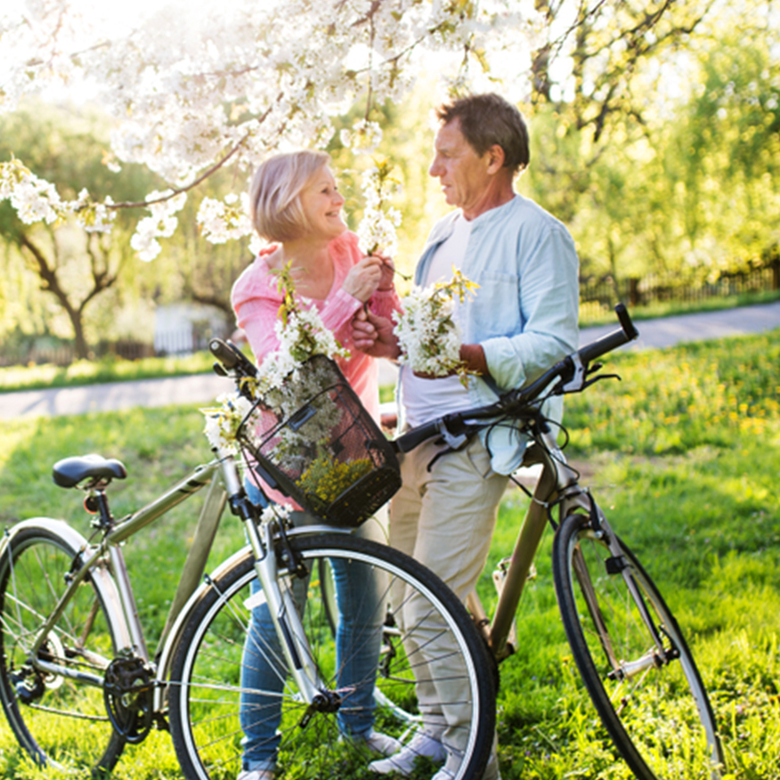 Supports Healthy Teeth & Bones – Middle-aged couple with their bicycles stopped under a flower tree chatting