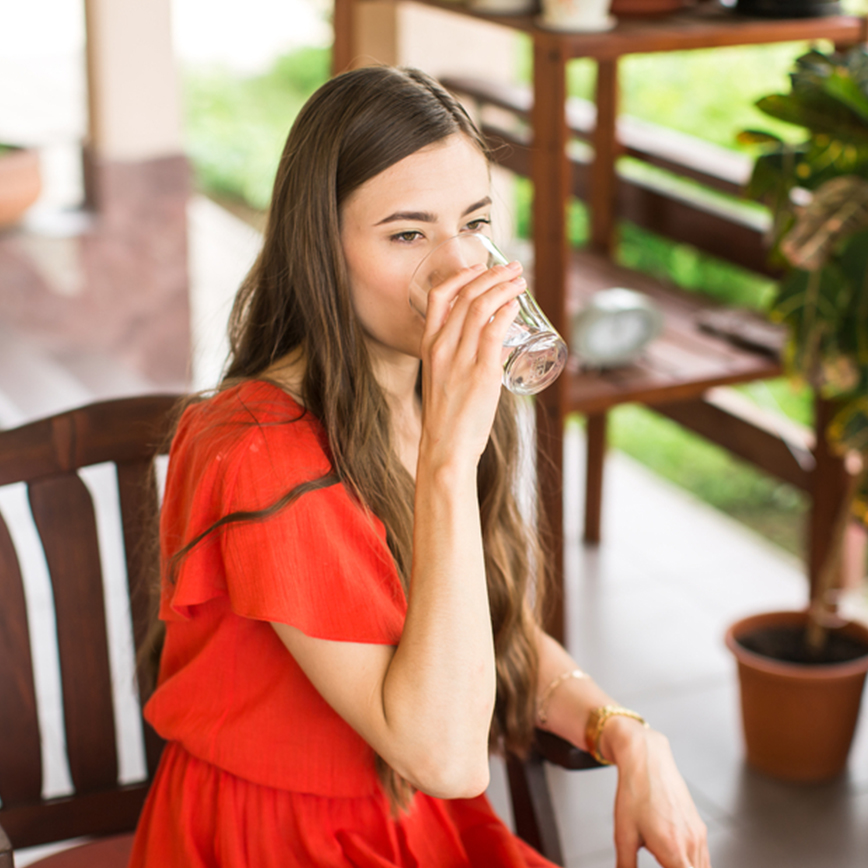 Supports Urinary Health – Young woman sitting on an outdoor patio and drinking a glass of water