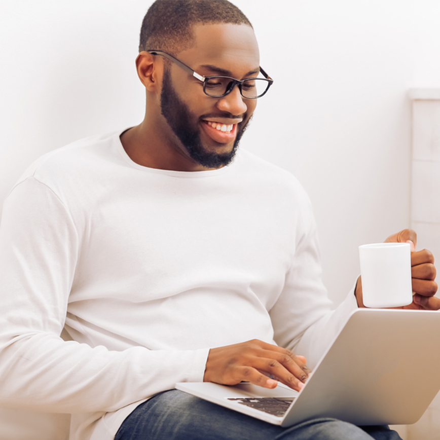 Boosts Total Wellness – Man sitting on couch with laptop and a cup of tea