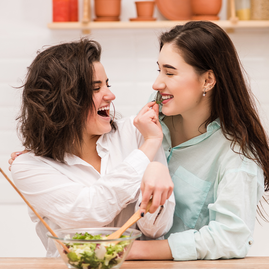Promotes a Healthy Microbiota – Two females tossing a salad in the kitchen