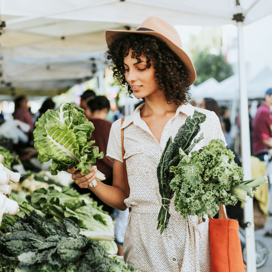 Relieves Digestive Issues - Woman choosing lettuce at a farmers market