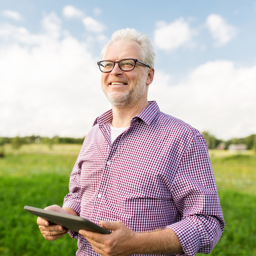 Encourages Bowel Regularity - Man standing in a field holding onto an iPad