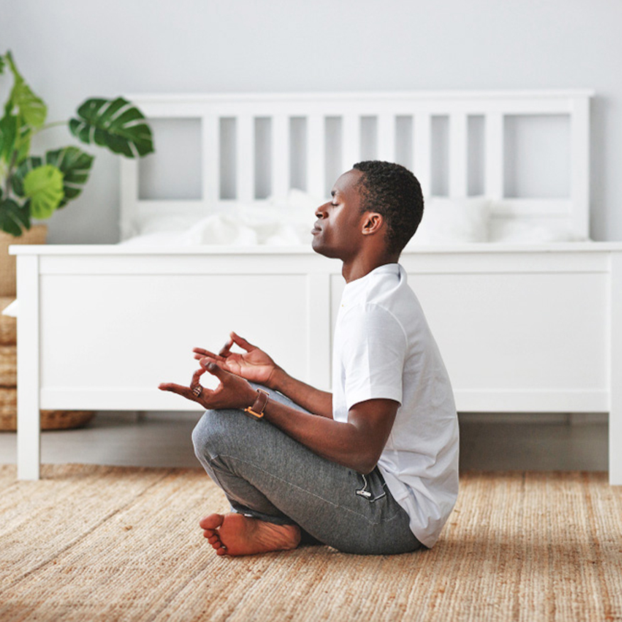 Normal Heart Health – Young black man meditating on rug at foot of bed in bedroom