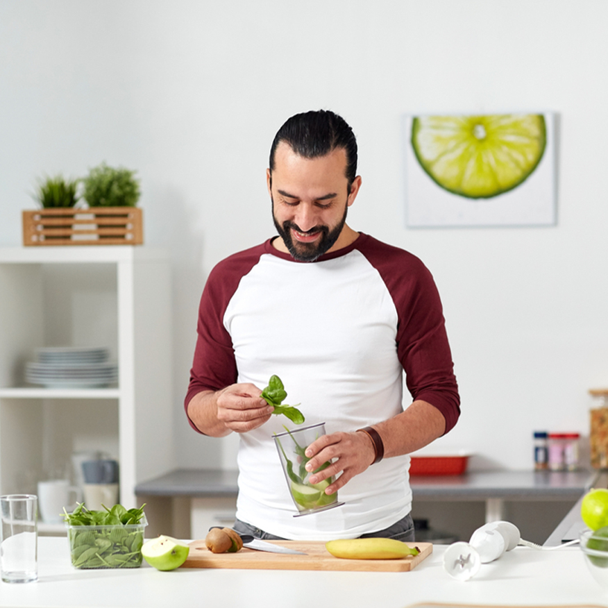 Amp Up Your Nutrition – Man adding organic vegetables to blender in the kitchen