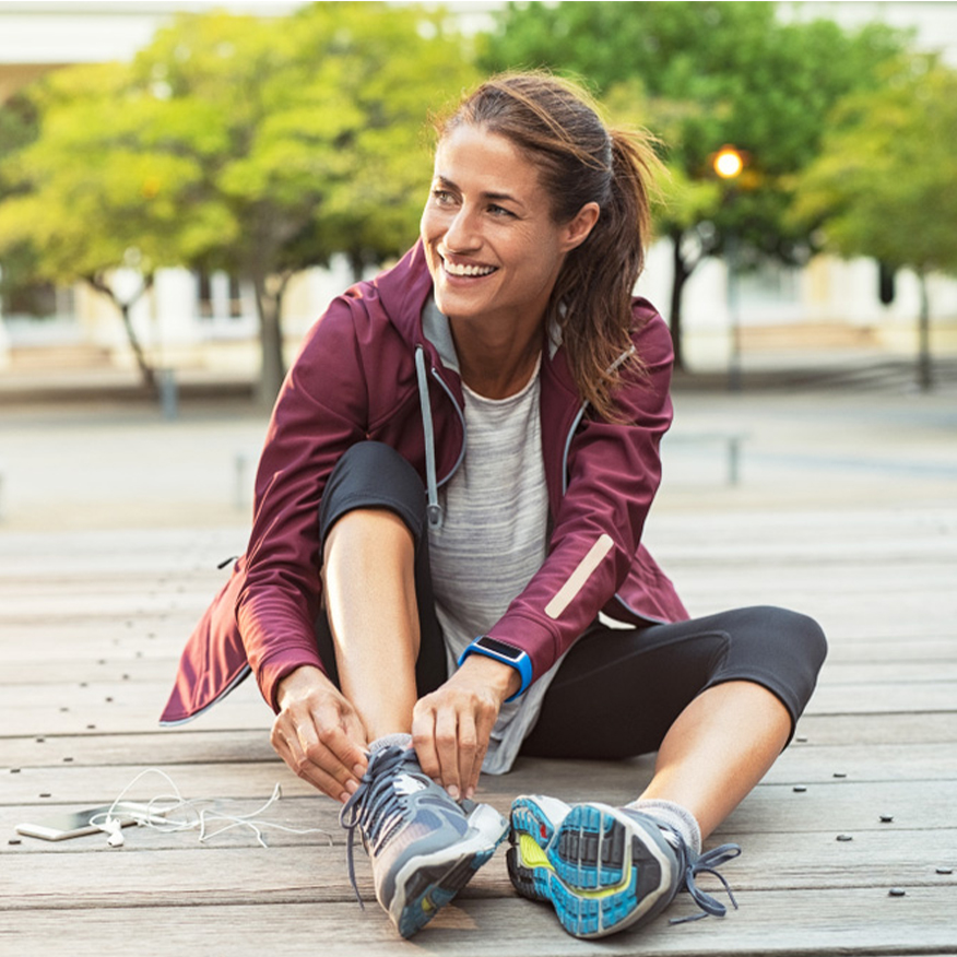 Activate Your Natural Energy – Woman sitting on wood plank in the park tying shoe
