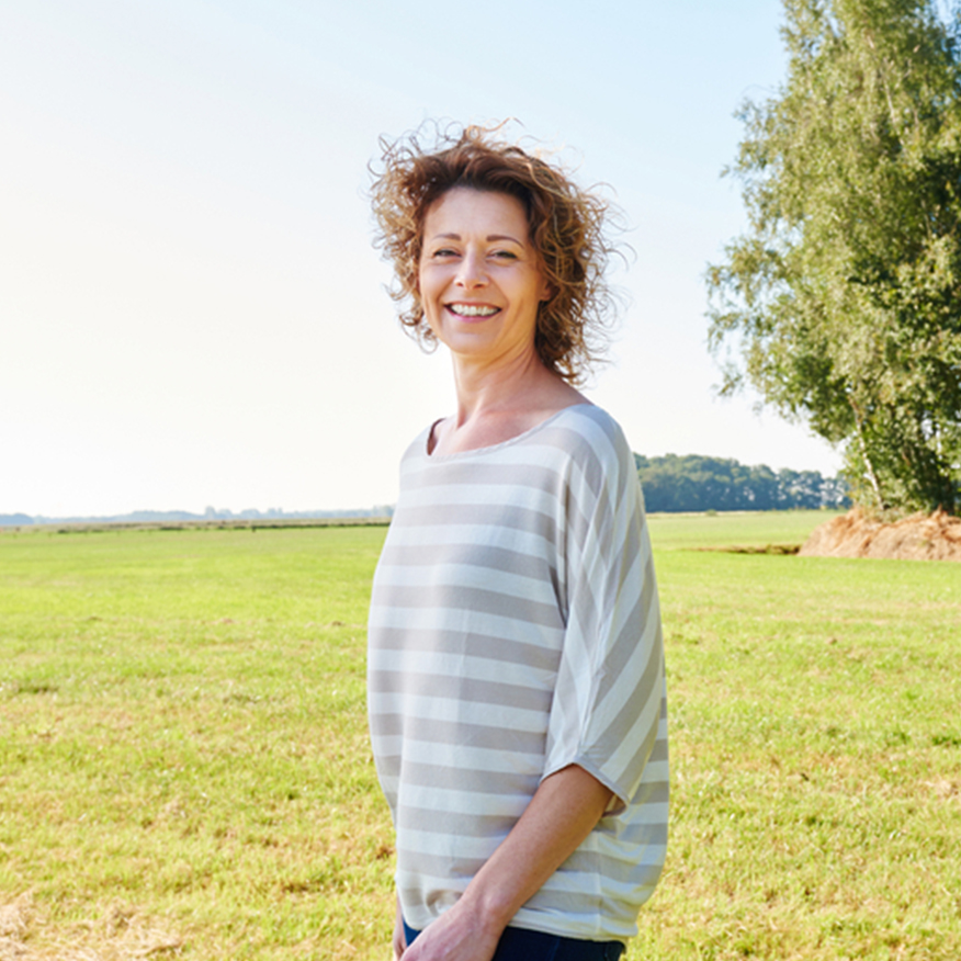 Soothe Redness & Swelling – Woman standing in a grass field smiling