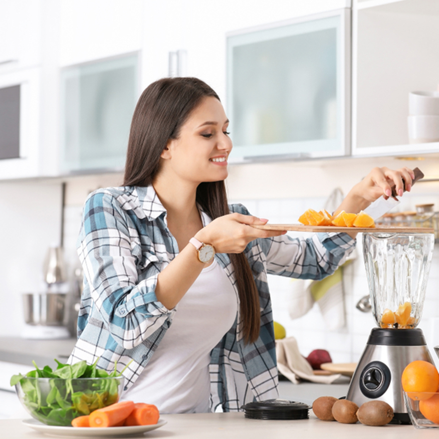 Supports Gut Health – Young woman adding organic ingredients into a blender