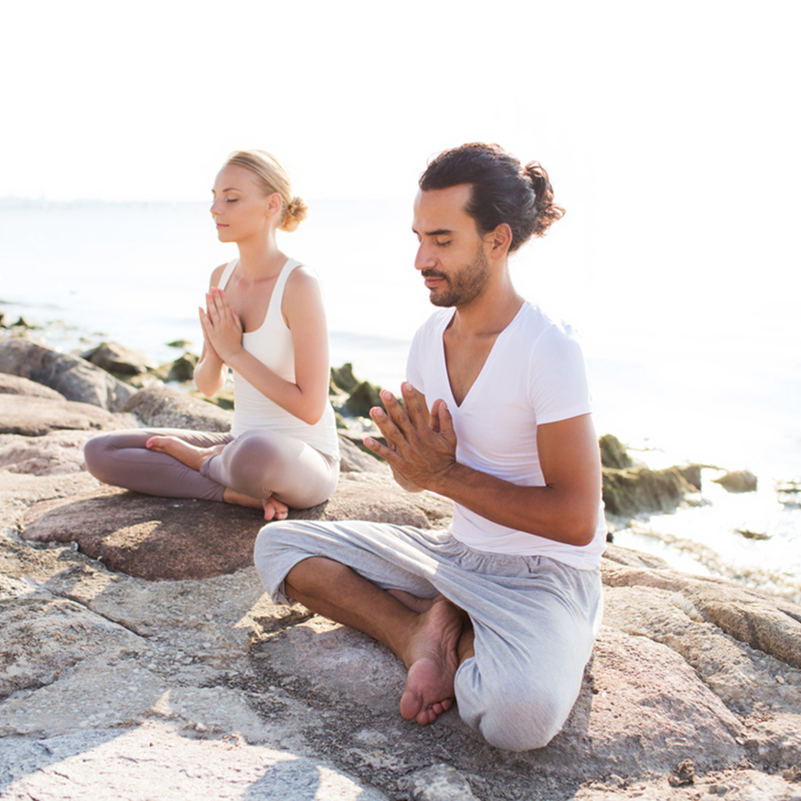 Promotes Overall Cleansing – Man and women practicing yoga atop rock cliff