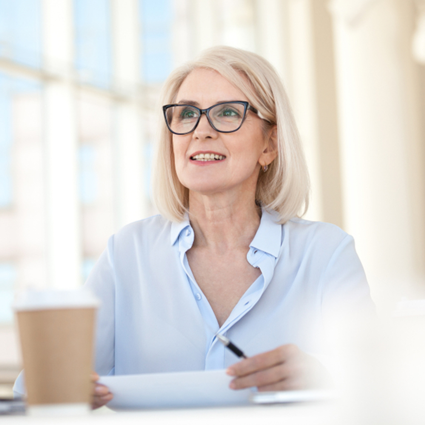 Heightens Clarity – Middle-aged woman sitting at a table taking a break and looking up from paperwork