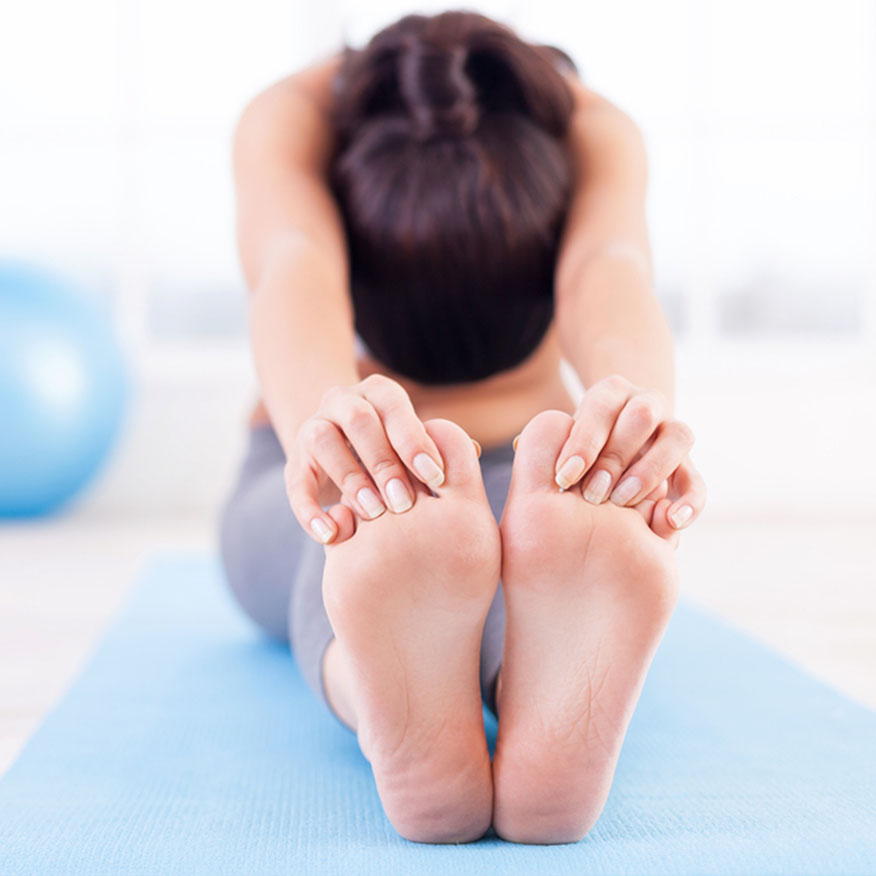 Keeps Toes Clear – Woman stretching on yoga mat with hands grabbing toes of feet