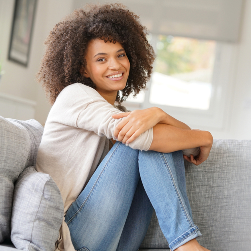 Supports Healthy Skin – Young woman comfortably resting on couch and smiling