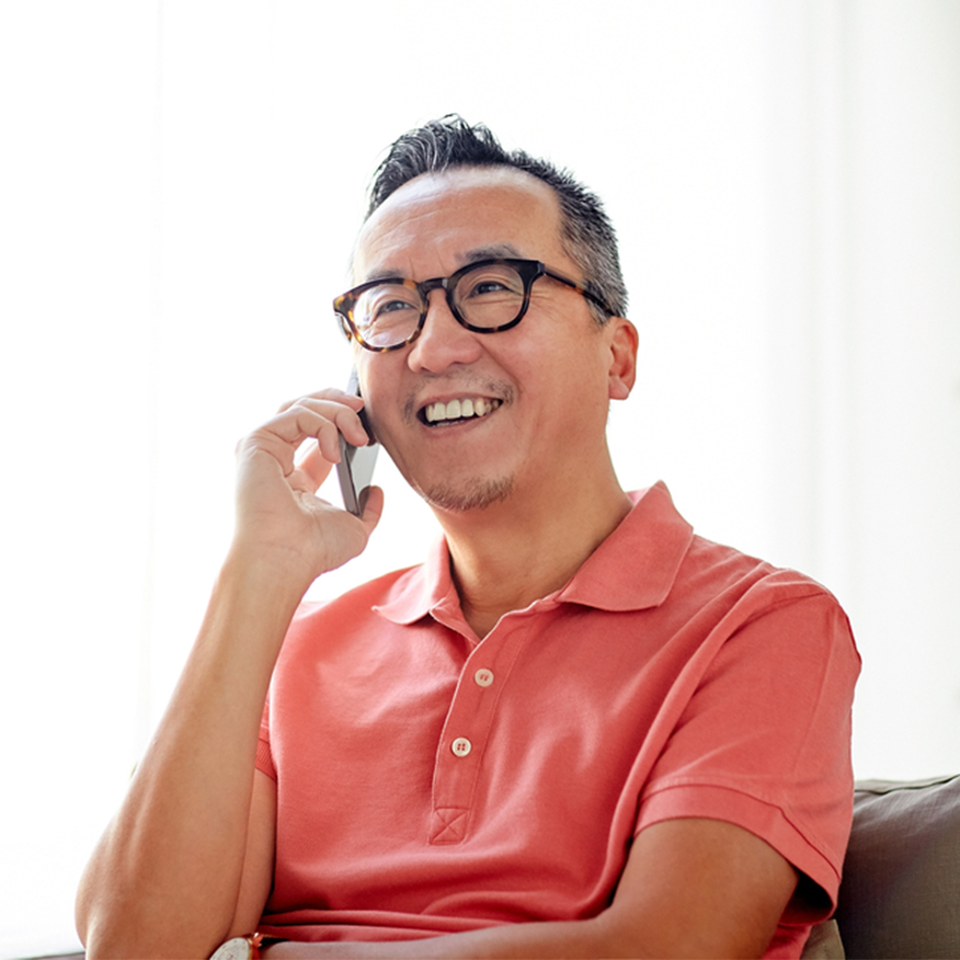 Perfect for All Skin – Middle-aged Asian man sitting on couch on his mobile phone