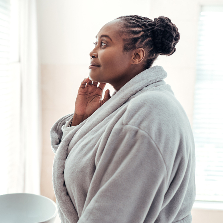 Up Your Skincare Routine – Black woman in robe checking face in the mirror in bathroom