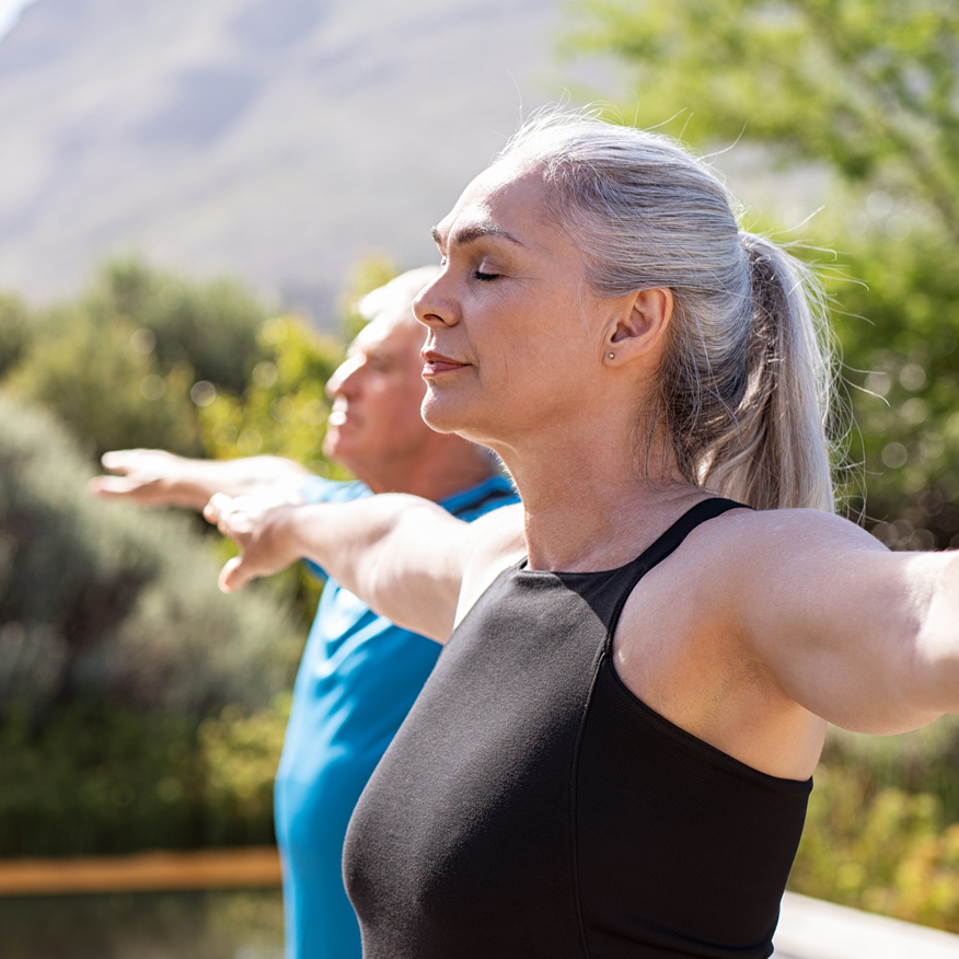 Promotes Heart Health – Man and woman practicing yoga outdoors