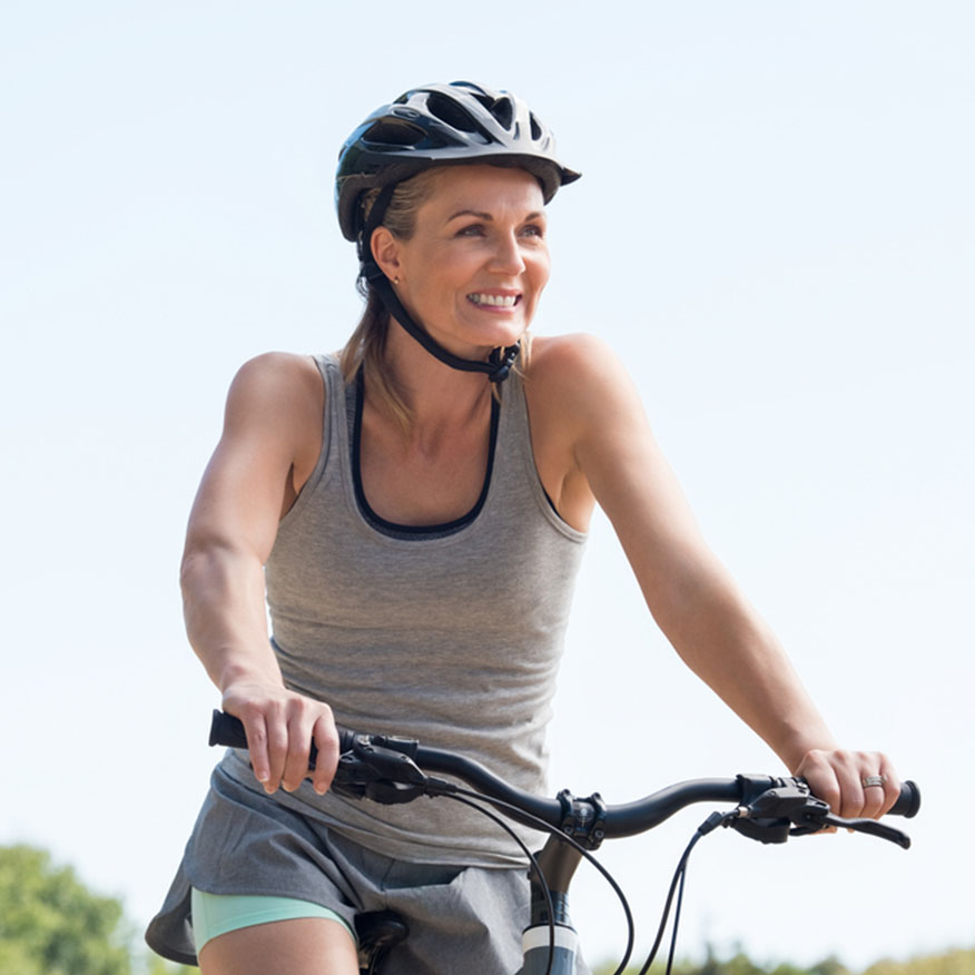 Promotes a Healthy Heart – Middle-aged woman wearing a helmet on a bicycle