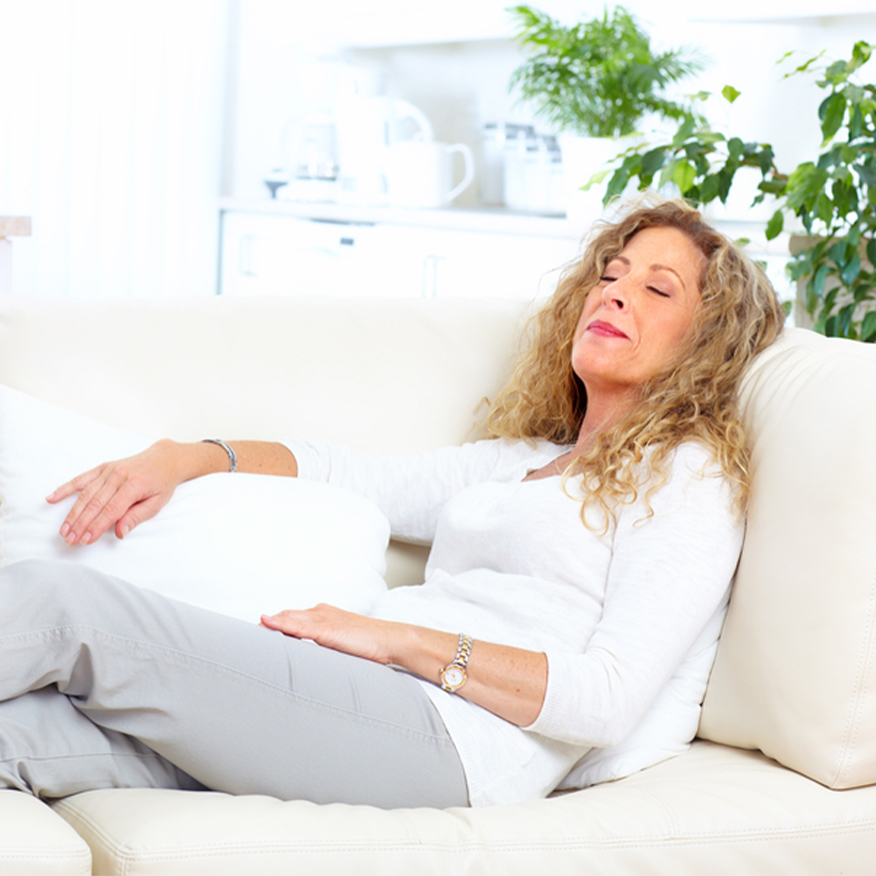 Supports Calmness – Middle-aged woman comfortably lounging on couch with eyes closed