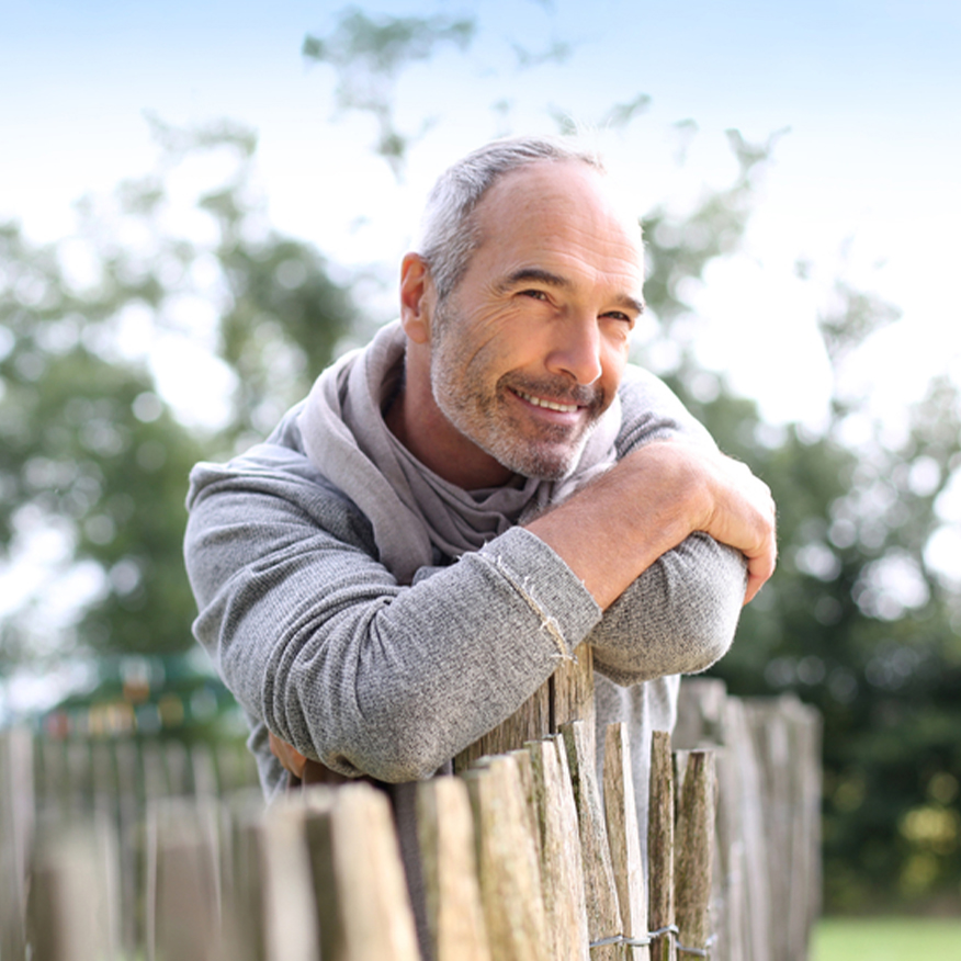 Soothes Anxious Feelings – Middle-aged man leaning against the top of a fence enjoying the sunlight