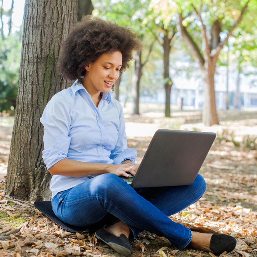 Encourages Clarity – Young woman sitting outdoor under a tree on her laptop