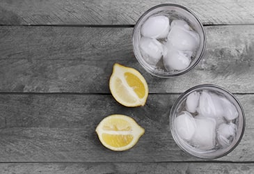 A glass of ice water next to a sliced lemon.