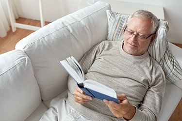 A person relaxing on a couch reading a book.
